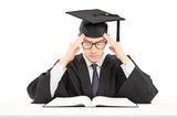 Student in graduation gown trying to concentrate on studying poster
