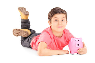Cheerful boy laying on the floor and holding a piggybank