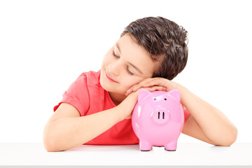 Cute male child sleeping on a piggybank