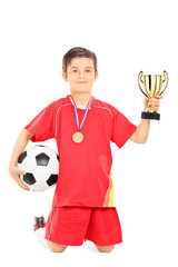 Junior football player holding a ball and golden cup