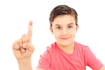Little kid showing his bandaged finger