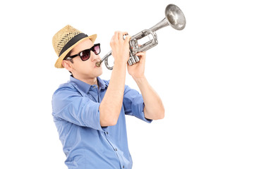 Young male musician blowing into a trumpet