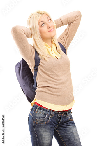 Young female student with backpack daydreaming