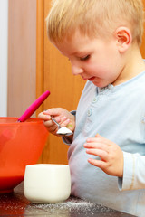 Boy kid baking cake. Child with spoon and sugar bowl. Kitchen.