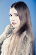 Girl with long hair. Young woman in fur coat on blue.
