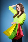 young woman with paper multi coloured shopping bag