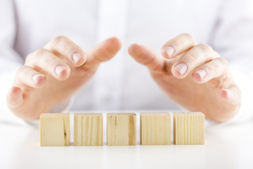 Man holding his hands over five blank wooden cubes