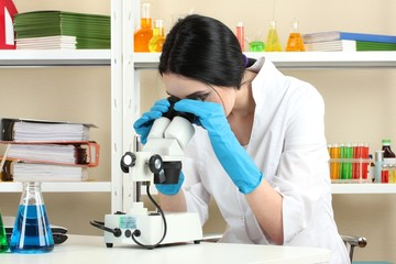 Young female scientist looking at microscope in chemistry