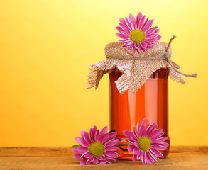 Sweet honey in jar on wooden table on yellow background