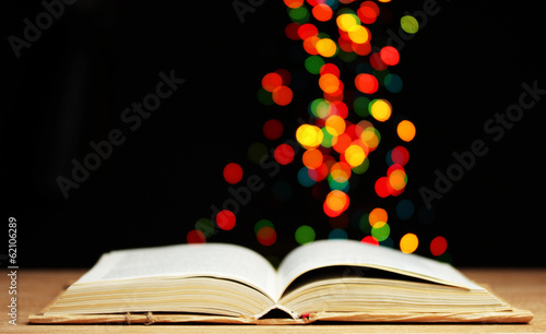 open book on wooden table on bright background