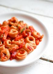 Tortellini primavera parmesan in marinara sauce on wooden rustic