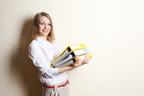 Portrait of businesswoman with folders near wall