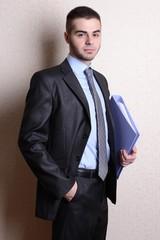 Portrait of businessman with folder near wall