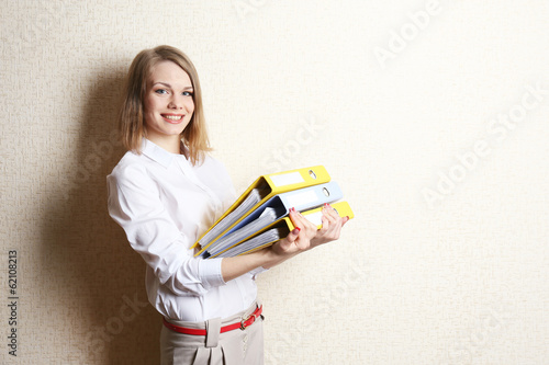 Leinwandbild Motiv Portrait of businesswoman with folders near wall