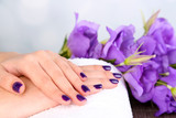 Beautiful woman hands with flowers on bright background