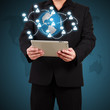 Businessman holding a tablet with globe and community icons. Con
