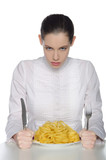 Woman with a plate of pasta and cutlery