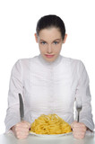 Woman with cutlery bent over a plate of pasta