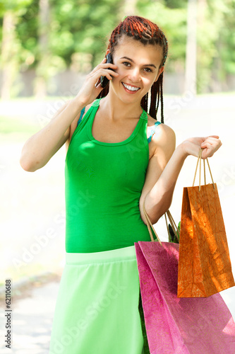 Happy girl with colorful shopping bags in the park