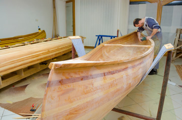 Young carpenter sanding new canoe in workshop