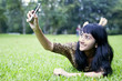 Asian woman taking picture with mobile phone at the park