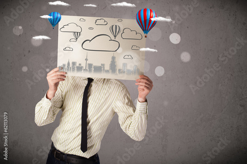 Businessman holding a cardboard with cityscape in front of his h