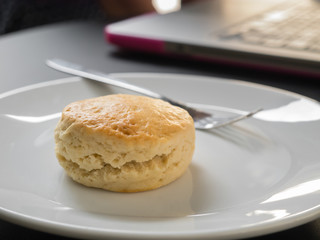 Scone on a white plate and laptop computer