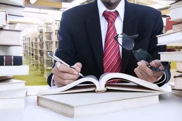 Businessman taking notes at library