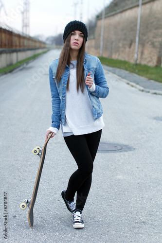 Teenager posing with skateboard