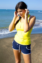 Woman relaxing listening music on the beach