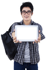 Male student showing copyspace on digital tablet
