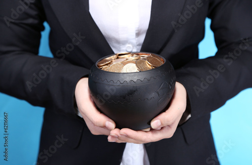 Ceramic pot with golden coins in female hands,