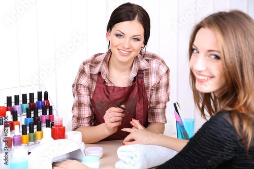 Beautiful girl manicurist doing manicure for woman in beauty