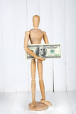 Wooden small mannequin with money on wooden background