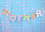 Mother- lettering of handmade paper letters on blue background