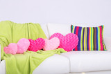 Pink heart shaped pillows, plaid on white sofa