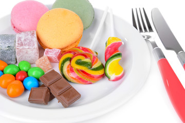 Different sweets on plate on table close-up