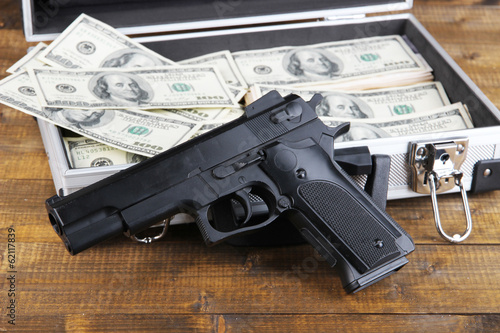 Case with money and gun, on wooden background