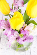 Flowers in vase with candles on wooden background