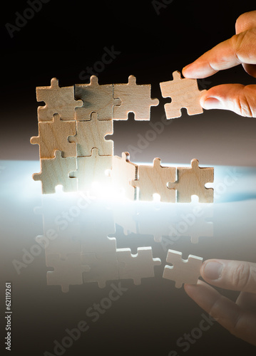 Wooden puzzle and backlight background. Close up