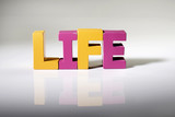 Multicolored word life made of wood.