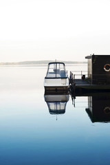 Boat and houseboat on calm morning lake. Blue horizon
