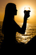 Silhouette of woman holding glass of wine during sunset