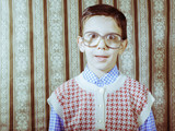 Smiling child with glasses in vintage clothes