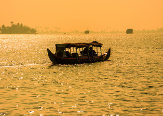 Sunset silhouette scene of a boat from the backwaters of Kerala,