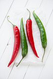 Red and green chili peppers over white wooden background