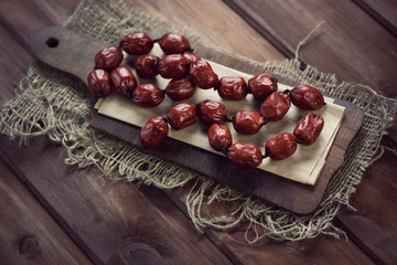 Rustic wooden chopping board with smoked mini sausages