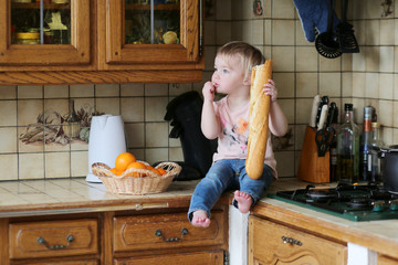 Funny blonde toddler girl sitting on the kitchen counter