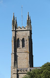 A Church Tower with a Flag Pole on Top.