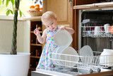 toddler girl helping in kitchen taking plates out of dish washer